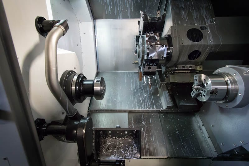 Inside a 6-Axis CNC Turning center with dual spindles and 24-tool turret.
